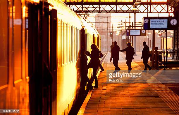 Passengers boarding train at sunset