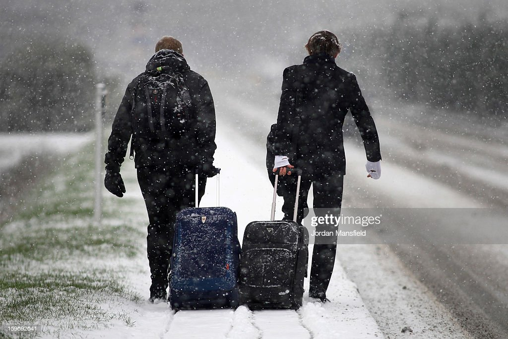 Passengers brave the snow on their way to Gatwick Airport on January 18, 2013 in London, United Kingdom. Widespread snowfall is affecting most of the UK with school closures and transport disruption. The Met Office has issued a red weather warning for parts of Wales, advising against all non-essential travel as up to 30cm of snow is expected to fall in some areas today.