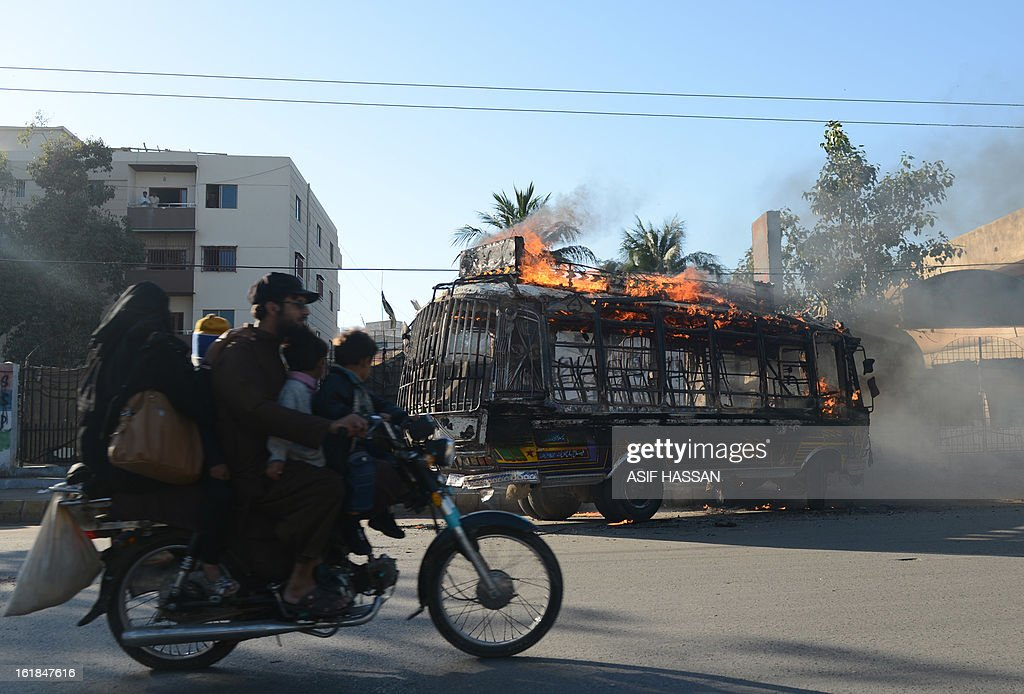 A passengers bus, set alight be demonstrators in retaliation of yesterday's bomb attack in Quetta, burns as commuters ride past in Karachi on February 17, 2013. The death toll from a devastating bomb attack on Shiite Muslims in southwest Pakistan rose to 81 Sunday, as the community threatened protests if swift action was not taken against the killers. AFP PHOTO/Asif HASSAN