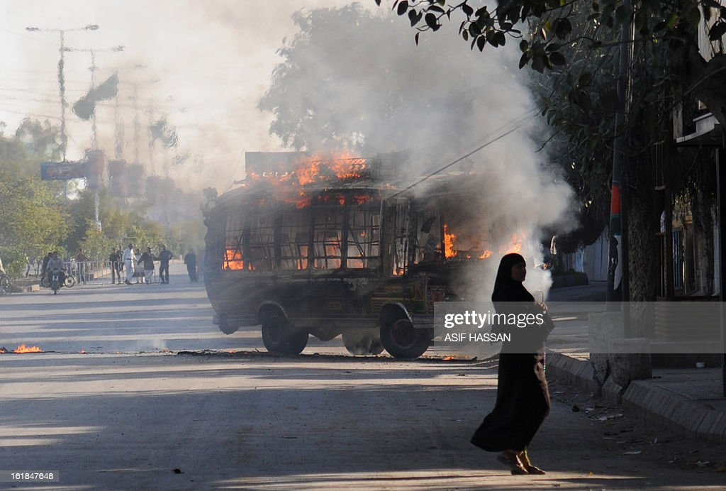 A passengers bus, set alight be demonstrators in retaliation of yesterday's bomb attack in Quetta, burns as a peestrian walks past in Karachi on February 17, 2013. The death toll from a devastating bomb attack on Shiite Muslims in southwest Pakistan rose to 81 Sunday, as the community threatened protests if swift action was not taken against the killers. AFP PHOTO/Asif HASSAN