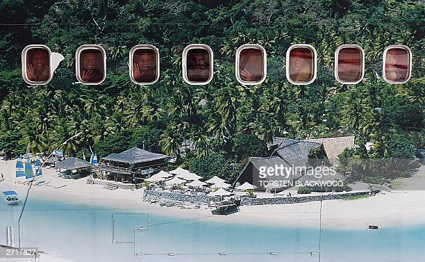 Passengers can be seen through the windows of an Air Pacific Boeing 747400 series aircraft featuring a mural of idyllic Castaway Island in the...