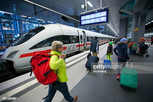 Passengers carry luggage on a platform as a Deutsche Bahn AG InterCity Express train manufactured by Siemens AG stands at Berlin Central Station in...