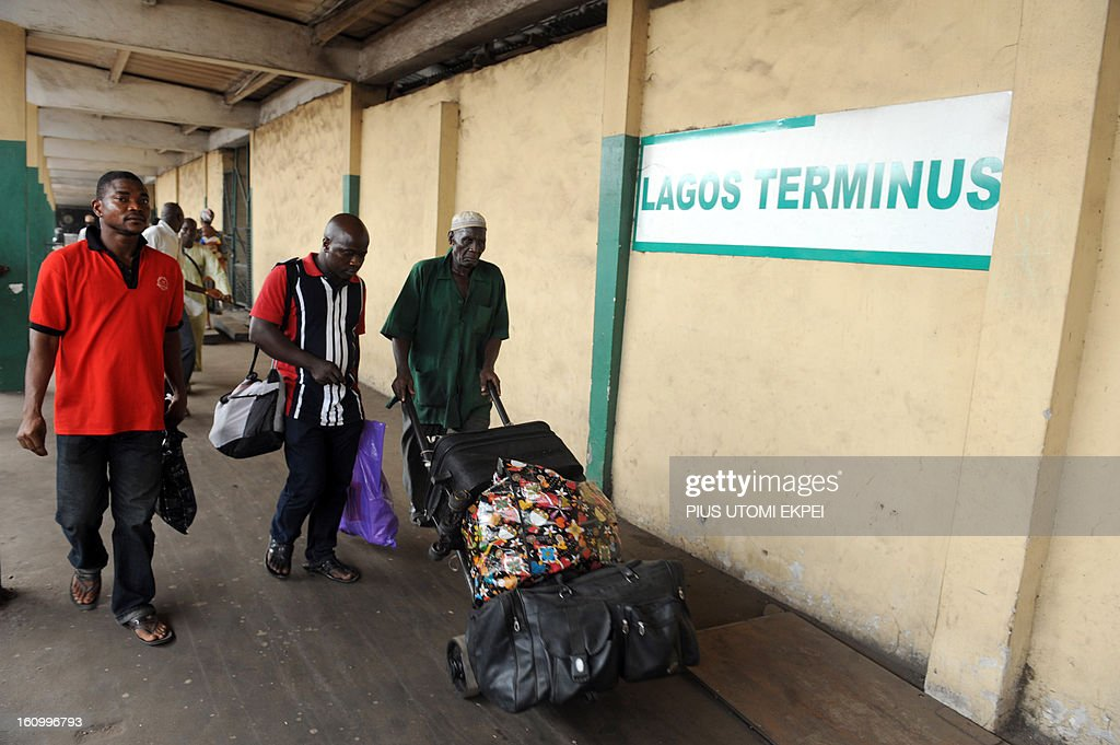 Passengers carry luggages before boarding a train at the Lagos Terminus on February 8, 2013. The rejuvenated Nigerian Railway Corporation has commenced operation of mass transit on the Lagos-Kano route, Nigeria's major commercial cities. The state-owned corporation which went into bankruptcy during the last 20 years due to lack of maintenance of infrastructure and high numbers of employees also began haulage of petroleum products from Lagos to the north of the country. Earlier last year, the Railway Corporation had acquired 20 pressurised tank wagons as it prepared to commence the fuel haulage. The 20 wagons have the capacity to lift 900,000 litres of petroleum products, the equivalent of 27 road tankers.