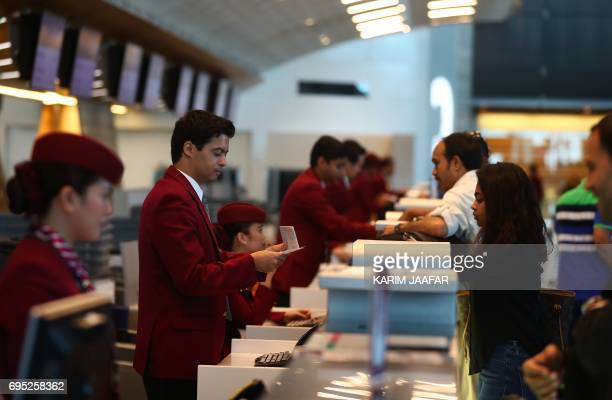 Passengers check in at the Hamad International Airport in the Qatari capital Doha on June 12 2017 Qatar Airways called on the UN's aviation body to...