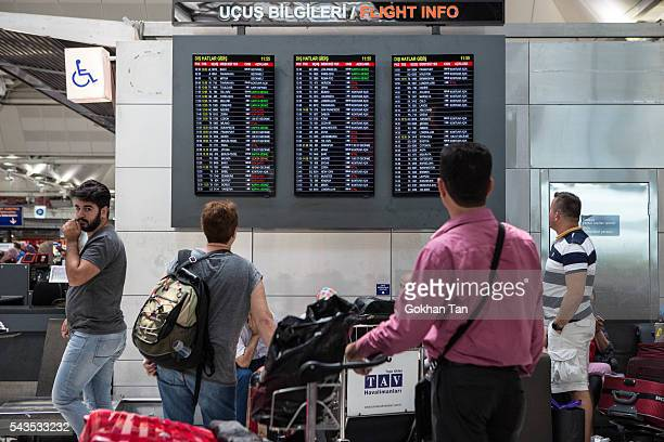 Passengers check the board shows status of flights at the country's largest airport Istanbul Ataturk following yesterday's blast June 29 2016 in...