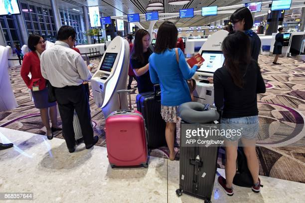 Passengers checkin for their flights using automated machines at the newlyopened Changi International Airport's Terminal 4 in Singapore on October 31...