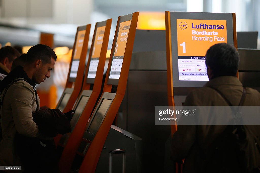Passengers collect boarding cards and flight tickets at electronic machines operated by Deutsche Lufthansa AG at Frankfurt airport in Frankfurt, Germany, on Thursday, March 14, 2013. Deutsche Lufthansa AG agreed to renew its short-haul fleet with 100 mostly fuel-efficient jets from Airbus SAS, as the airline seeks to cut kerosene costs that constitute its single biggest expense. Photographer: Ralph Orlowski/Bloomberg via Getty Images