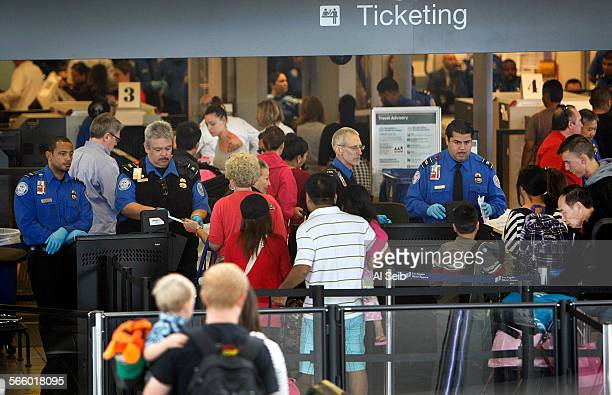 Passengers continue through the screening area in LAX terminal three on Monday morning November 04 2013 after a deadly shooting Friday at terminal...