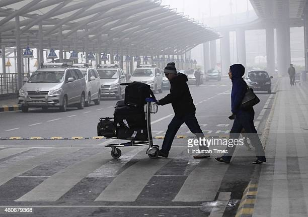 Passengers crossing a road towards parked taxies in a dense foggy morning at the International Airport on December 18 2014 in New Delhi India The...