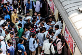 Passengers disembark as commuters wait to board a train during the morning rush hour at Kurla railway station in Mumbai India on Wednesday April 15...