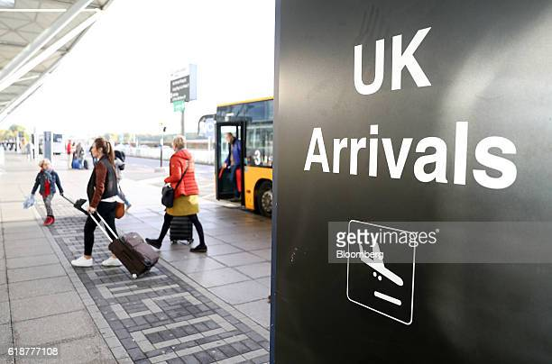 Passengers disembark buses next to an arrivals sign at London Stansted Airport operated by Manchester Airports Group in Stansted UK on Friday Oct 28...