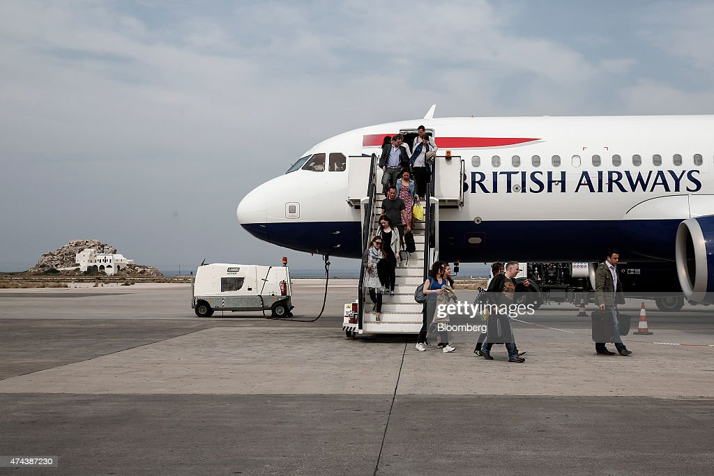 Passengers disembark from a passenger jet operated by British Airways a unit of IAG SA at the arrivals terminal at Santorini airport on the island of...
