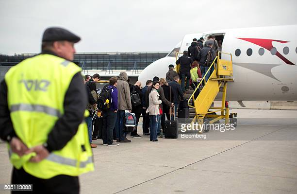 Passengers embark an Austrian Airlines AG aircraft on the tarmac at Vienna International Airport operated by Flughafen Wien AG in Vienna Austria on...