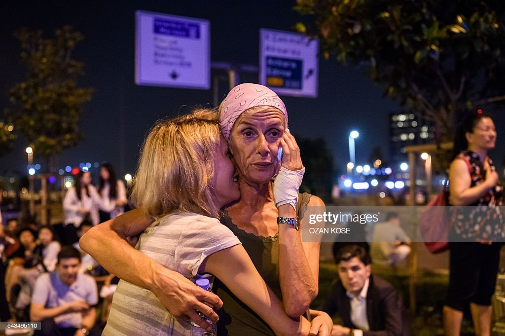 Passengers embrace outside Ataturk airport`s main enterance in Istanbul, on June 28, 2016, after two explosions followed by gunfire hit Turkey's largest airport, killing at least 10 people and injuring 20. All flights at Istanbul's Ataturk international airport were suspended on June 28, 2016 after a suicide attack left at least 36 people dead. / AFP / OZAN