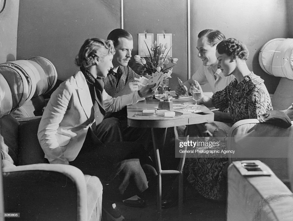 Passengers enjoying a drink and a game of cards in the cabin of an Imperial Airways plane.