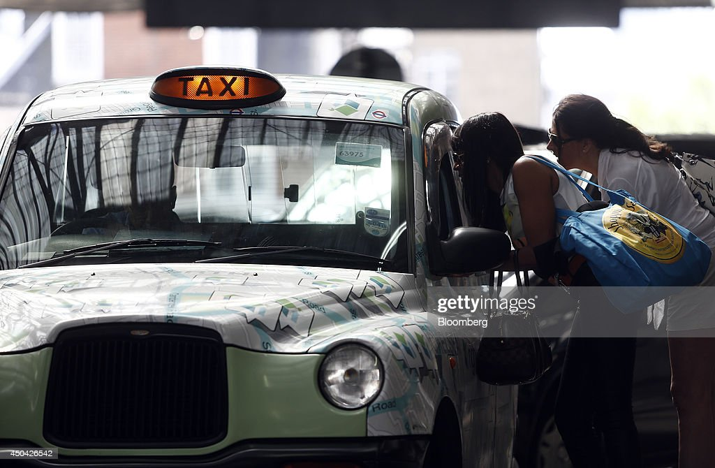 Passengers enquire about a fare before boarding a London taxi cab outside Waterloo train station, ahead of a protest against Uber Technologies Inc.'s car sharing service, in London, U.K., on Wednesday, June 11, 2014. More than 30,000 taxi and limo drivers from London to Milan plan to cause traffic snarls in tourist centers and shopping districts, in protest against the unregulation of Uber's car-sharing service. Photographer: Simon Dawson/Bloomberg via Getty Images