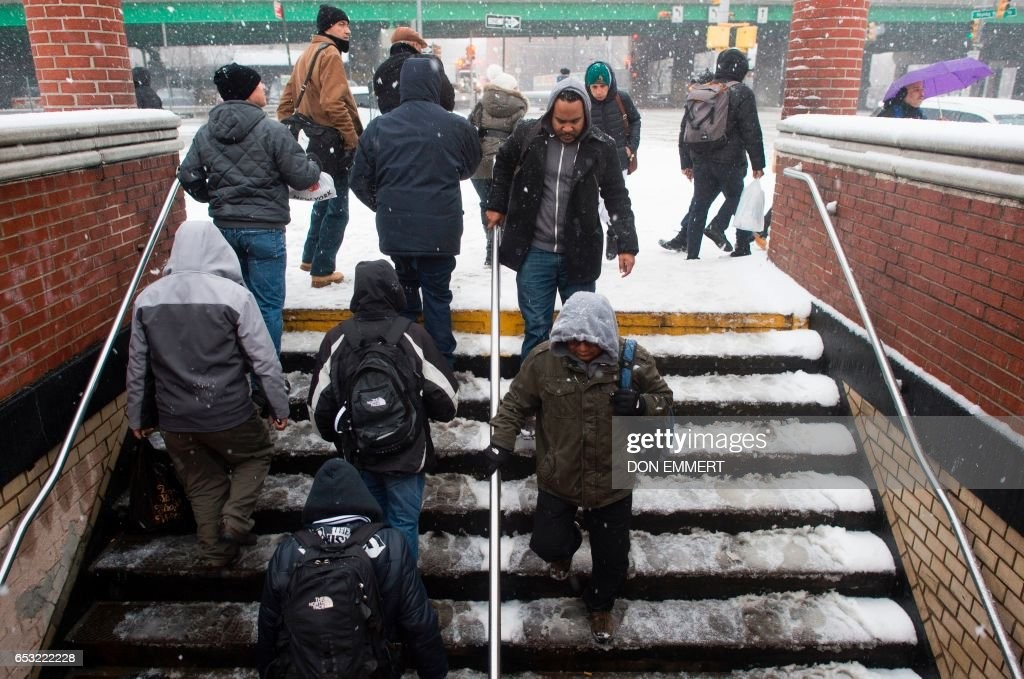 Passengers enter and exit the Hunts Point subway station in the Bronx Borough March 14, 2017 in New York. Winter Storm Stella dumped snow and sleet Tuesday across the northeastern United States where thousands of flights were canceled and schools closed, but appeared less severe than initially forecast. After daybreak the National Weather Service (NWS) revised down its predicted snow accumulation for the city of New York, saying that the storm had moved across the coast. EMMERT