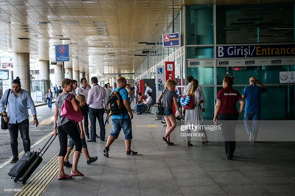 Passengers enter the Ataturk airport International arrival terminal on June 29, 2016 as an employee of a private security company patrols (2nd R), a day after a suicide bombing and gun attack targeted Istanbul's airport, killing at least 36 people. A triple suicide bombing and gun attack that occurred on June 28, 2016 at Istanbul's Ataturk airport has killed at least 36 people, including foreigners, with Turkey's prime minister saying early signs pointed to an assault by the Islamic State group. / AFP / OZAN