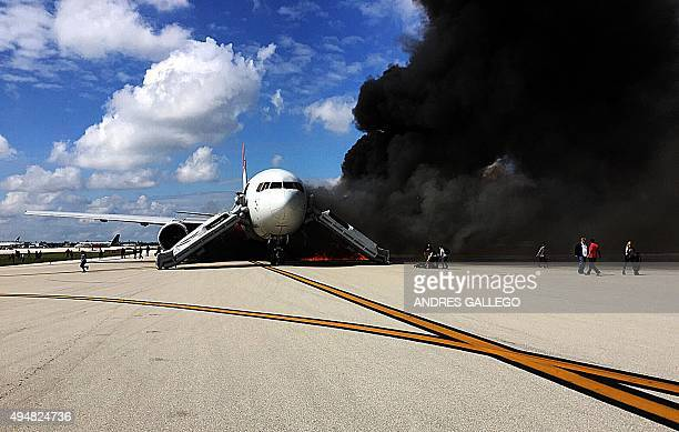 Passengers evacuate from the plane on fire at Fort Lauderdale airport Florida on October 29 2015 An airliner caught fire on a runway at Fort...