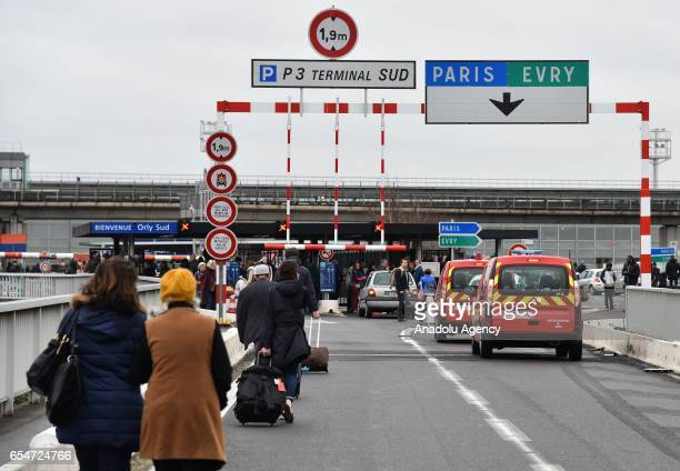 Passengers evacuated from Orly airport walk on the highway at Orly airport near Paris France on March 18 2017 following the shooting of a man by...