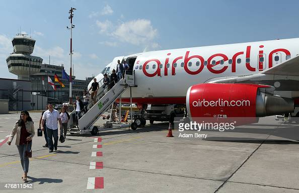 Passengers exit an Air Berlin airplane after their flight from Frankfurt on the tarmac at Tegel airport on June 10 2015 in Berlin Germany The airline...