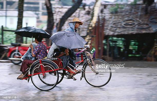 Passengers facing front and rear, each sheltered by umbrella, rainy day sai kaa swooshes home from market.