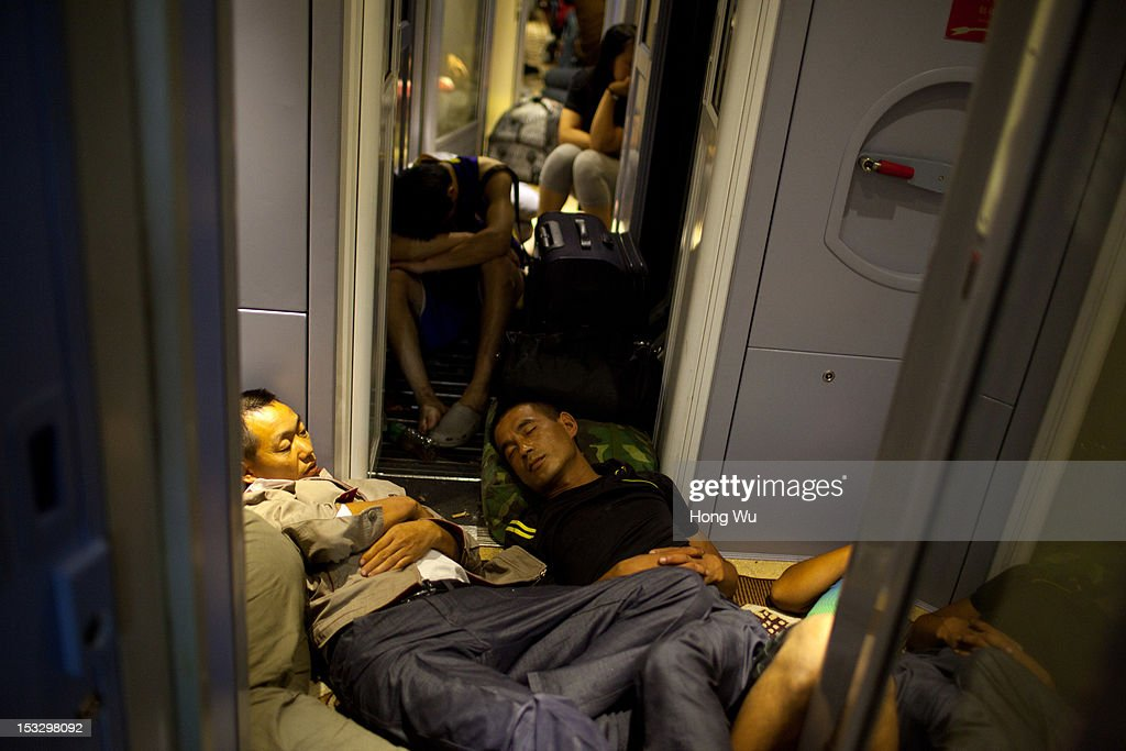Passengers fall asleep in a train carriage of from Beijing to Lhasa on August 14, 2012 in Wuzhong, China. After Qinghai-Tibet Railway went into operation on July 1, 2006, connecting China's capital Beijing and Lhasa of Tibet Autonomous Region by 4,064 km of railway line. Passengers and supplies are transported by train on this the world's highest railway to Tibet.