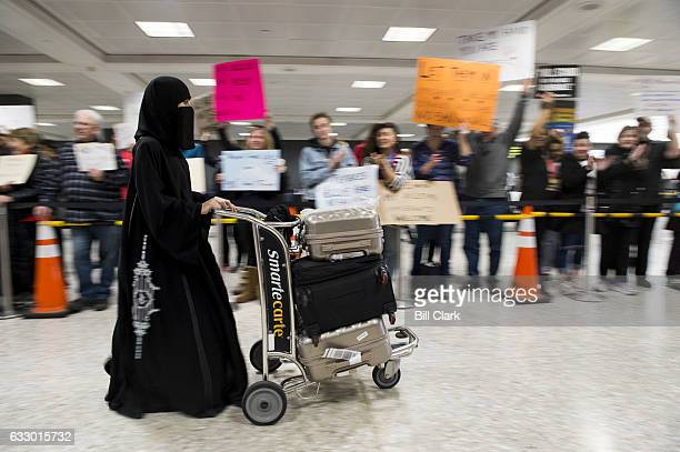 Passengers from a Saudi Arabian Airlines flight from Jeddah are greeted by protesters as they arrive at Dulles International Airport in Virginia on...