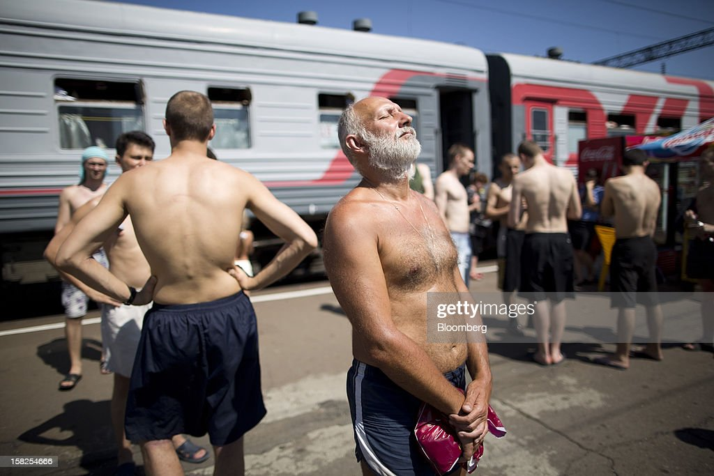 Passengers from the Novorossiysk-Moscow train, operated by OAO Russian Railways, sunbathe on a platform at Liski station in Voronezh region, Russia, on Sunday, July 15, 2012. Russia's government plans to sell stakes in its rail monopoly, grain trader, biggest shipper, nanotechnology holding and largest banks within 18 months as it loosens its grip on an economy dominated by commodity exports. Photographer: Andrey Rudakov/Bloomberg via Getty Images