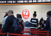 Passengers gather at a Japan Airlines checkin counter at Tokyo's Haneda airport on January 31 2014 Japan's two biggest airlines said January 31 that...