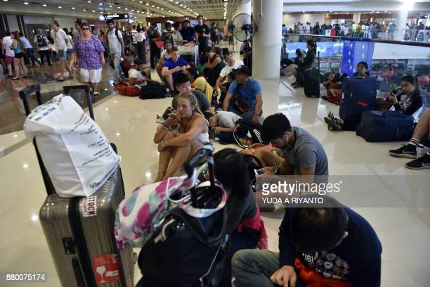 Passengers gather at the Gusti Ngurah Rai International airport in Denpasar Bali on November 27 after flights were cancelled due to the threat of an...