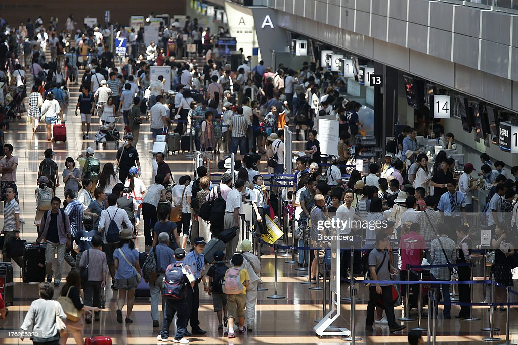 Passengers gather in the departure lobby at Haneda Airport in Tokyo Japan on Sunday Aug 11 2013 Japan's gross domestic product rose an annualized 26...