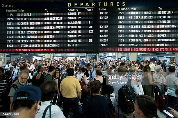 Passengers gather near the departures board at Penn Station July 1 2016 in New York City Officials from the American Automobile Association are...