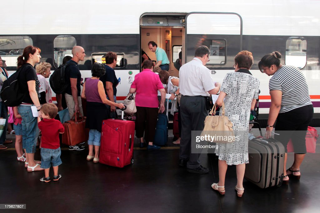Passengers gather to board a train operated by Renfe Operadora SC as it sits at a platform at Atocha train station in Madrid, Spain, on Saturday, Aug. 3, 2013. Spain's state-owned rail operator Renfe plans to cut almost 500 jobs, or 4% of staff, as early as this year, ABC reports, citing comments by Public Works Minister Ana Pastor. Photographer: Antonio Heredia/Bloomberg via Getty Images