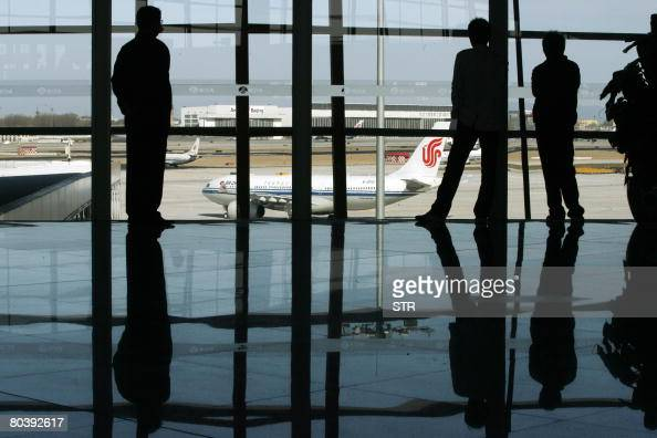 Passengers gather to watch as Air China's jetliners move into the tarmac of the new jumbo Terminal 3 at the Beijing Capital International Airport in...