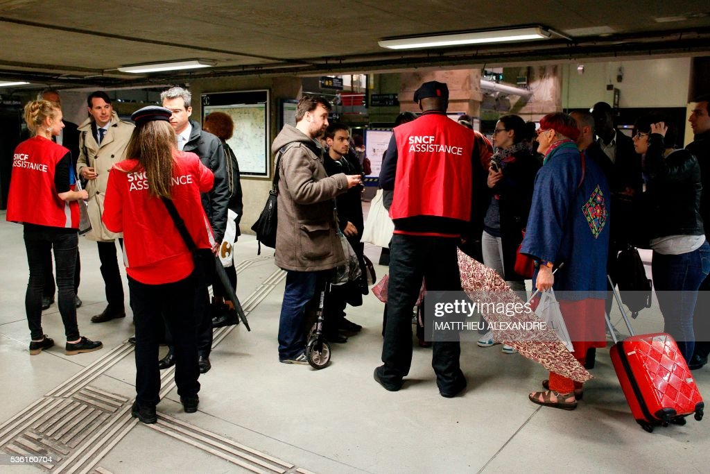 Passengers get information in the Gare Montparnasse rail station in Paris, on May 31, 2016, at the start of a strike by employees of French state-owned rail operator SNCF to protest against government labour reforms. France is bracing for a week of severe disruption to transport after unions called for more action in their bitter standoff with the Socialist government over its labour market reforms. / AFP / MATTHIEU