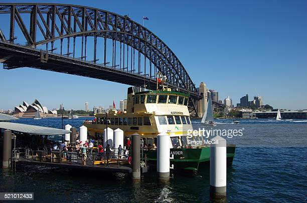Passengers get on and off a ferry on a sunny day at Milsons Point Ferry Wharf with the Sydney Harbour Bridge and Sydney Opera House in the background...