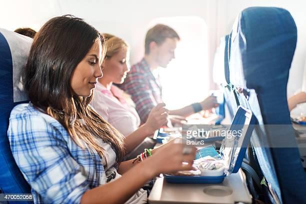 Los pasajeros tienen un almuerzo mientras está de viaje en avión.