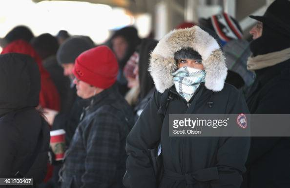 Passengers heading into downtown wait on an 'L' platform for the train to arrive in below zero temperatures on January 7 2014 in Chicago Illinois...