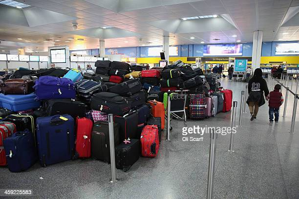 Passengers' hold luggage is stacked in the departure hall of Gatwick airport's North Terminal as severe weather has caused delays and cancellations...