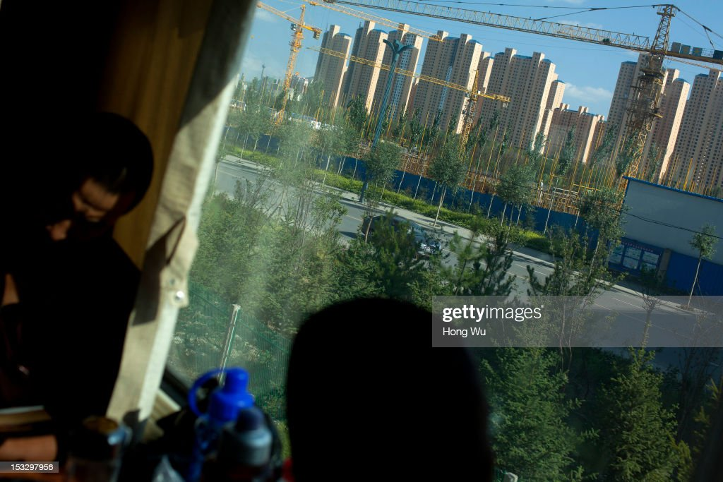 Passengers in a train carriage of from Beijing to Lhasa passing by new apartments on August 14, 2012 in Xining, China. After Qinghai-Tibet Railway went into operation on July 1, 2006, connecting China's capital Beijing and Lhasa of Tibet Autonomous Region by 4,064 km of railway line. Passengers and supplies are transported by train on this the world's highest railway to Tibet.