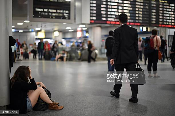 Passengers injured in an Amtrak train derailment who were bused from to New York from Philadelphia walk through Penn Station May 13 2015 in New York...