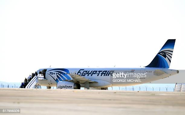 TOPSHOT Passengers leave an EgyptAir Airbus A320 sitting on the tarmac of Larnaca airport after it was hijacked and diverted to Cyprus on March 29...