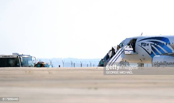 Passengers leave an EgyptAir Airbus A320 sitting on the tarmac of Larnaca airport after it was hijacked and diverted to Cyprus on March 29 2016 A...