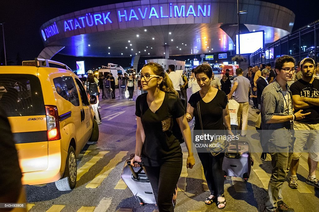 Passengers leave Ataturk airport in Istanbul on June 28, 2016 after two explosions followed by gunfire hit Turkey's biggest airport, killing at least 28 people and injuring 20. All flights at Istanbul's Ataturk international airport were suspended on June 28, 2016 after a suicide attack left at least 10 people dead and 20 others wounded, Turkish television stations reported. / AFP / OZAN