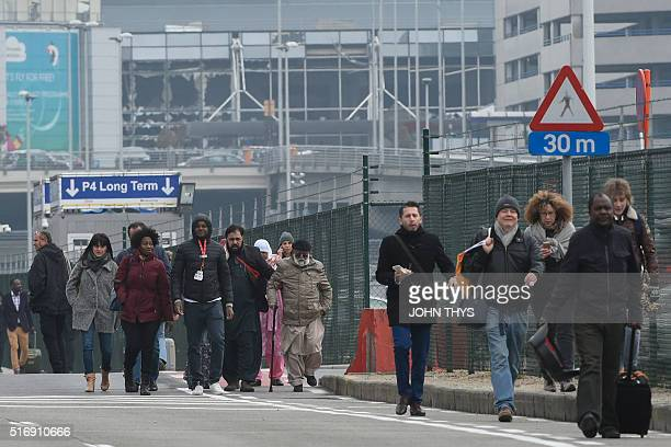 TOPSHOT Passengers leave Brussels airport on March 22 2016 in Zaventem following its evacuation after at least 13 people were killed and 35 injured...