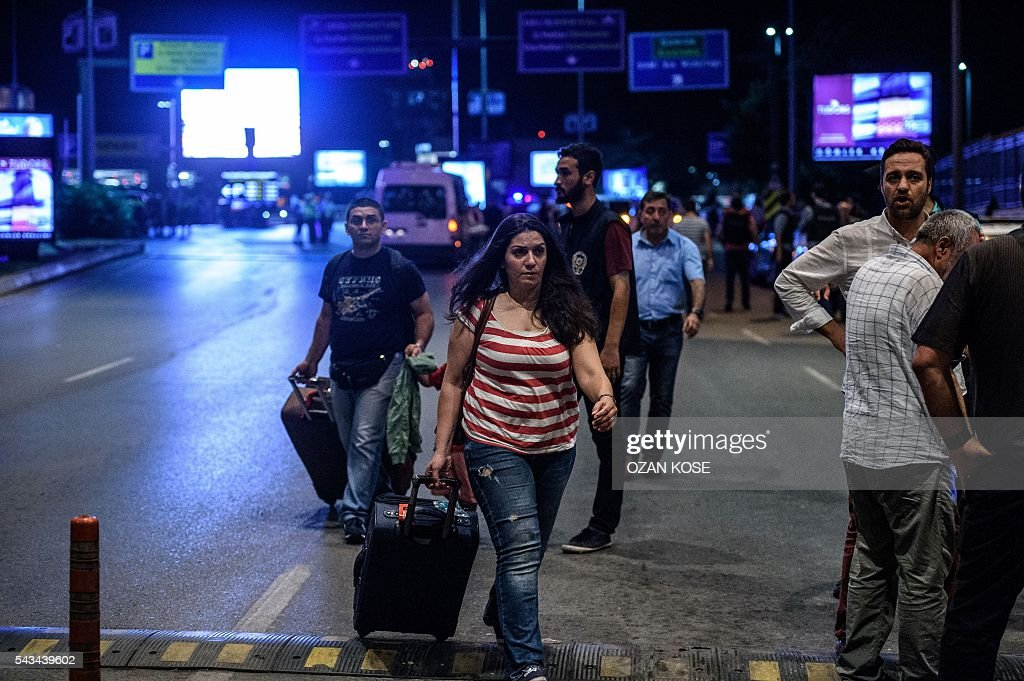 Passengers leave the Ataturk airport in Istanbul, on June 28, 2016, after two explosions followed by gunfire hit the Turkey's biggest airport, killing at least 10 people and injured 20. All flights at Istanbul's Ataturk international airport were suspended on June 28, 2016 after a suicide attack left at least 10 people dead and 20 others wounded, Turkish television stations reported. / AFP / OZAN