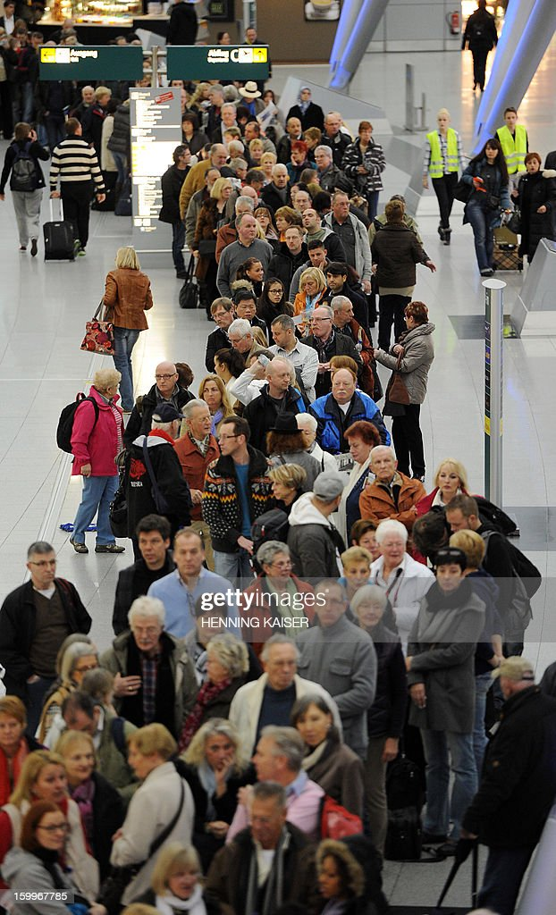 Passengers line up at the airport in Duesseldorf, western Germany, on January 24, 2013. Security staff at the airport staged a strike to demand higher pay, leading to the cancellation of dozens of flights. At Germany's third biggest airport in Duesseldorf, some 94 flights were cancelled during the morning, out of a total of 528 arrivals and departures scheduled for the day, according to information from the airport. AFP PHOTO / HENNING KAISER GERMANY OUT