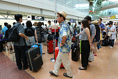 Passengers line up in front of the baggage dropoff counter for All Nippon Airways Co in the departure lobby at Haneda Airport in Tokyo Japan on...