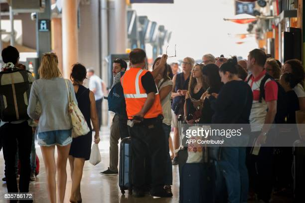 Passengers listen to an official as they wait for their trains at The SaintCharles Station in Marseille on August 20 following a fire between Aubagne...